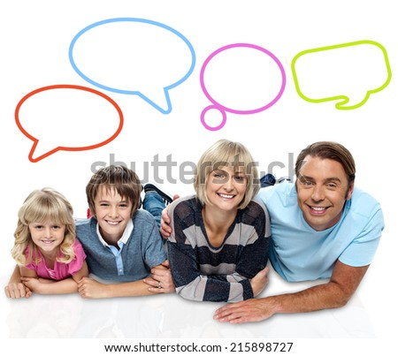 Smiling family of four with speech bubbles - stock photo