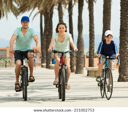smiling family of three cycling over city in summer day - stock photo
