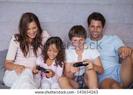 Smiling family playing video games on bed - stock photo
