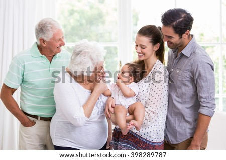 Smiling family playing with baby at home - stock photo