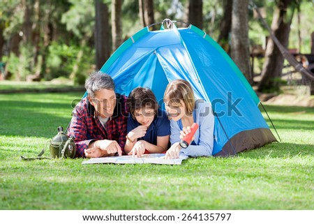 Smiling family reading map at campsite in park - stock photo
