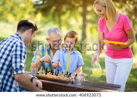 smiling family relaxing playing chess in the park - stock photo