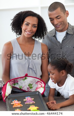 Smiling family showing handmade cookies in the kitchen - stock photo