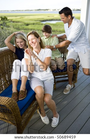 Smiling family sitting and laughing together outdoors on terrace - stock photo