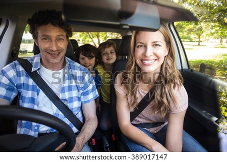 Smiling family sitting in the car and driving - stock photo