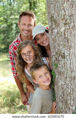 Smiling family standing behind a tree - stock photo