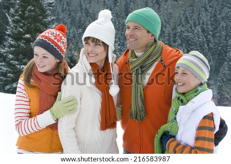 Smiling family standing in snow - stock photo