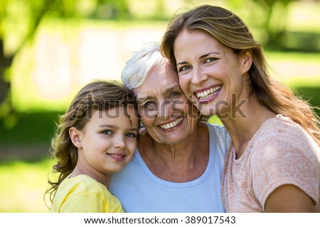 Smiling family standing in the garden - stock photo