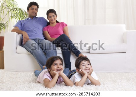 Smiling family watching TV - stock photo