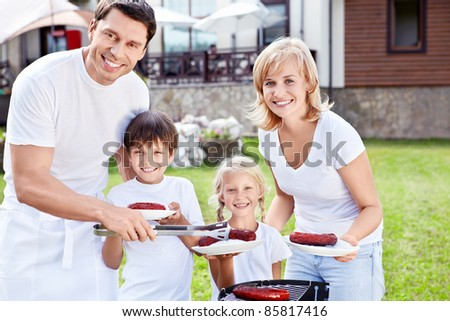 Smiling family with children at barbecue - stock photo