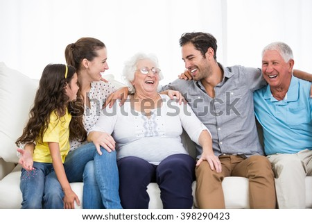 Smiling family with grandparents discussing at home - stock photo