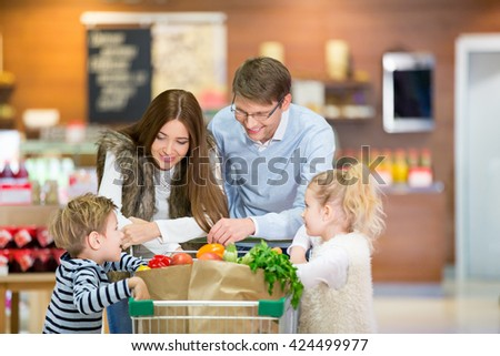 Smiling family with shopping cart - stock photo