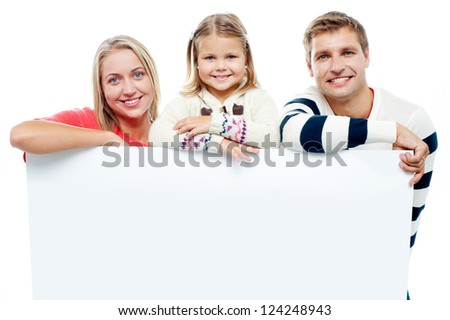 Smiling family with whiteboard in a studio looking at camera - stock photo