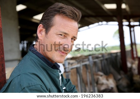 Smiling farmer standing in barn - stock photo