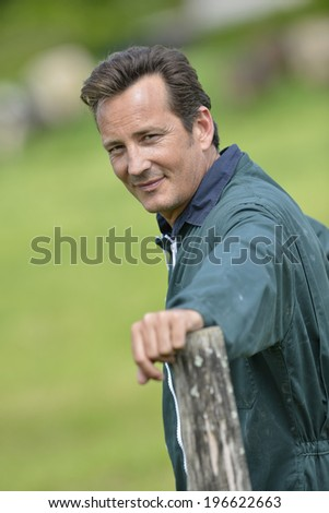Smiling farmer standing in country field - stock photo