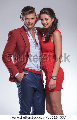 smiling fashion couple posing in studio on grey background - stock photo