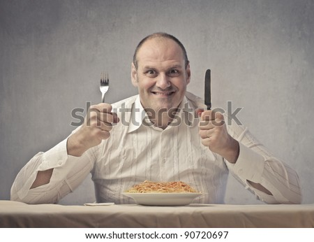 Smiling fat man in front of a plate of spaghetti - stock photo