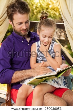 Smiling father and daughter reading book during sunny summer day. Happy family time outdoor on garden terrace - countryside weekend or holiday concept. - stock photo