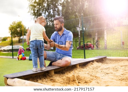 Smiling father and his little daughter playing on playground. - stock photo