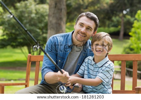 Smiling father and son fishing while sitting on park bench - stock photo