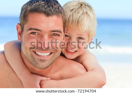 Smiling father having son a piggyback at the beach - stock photo