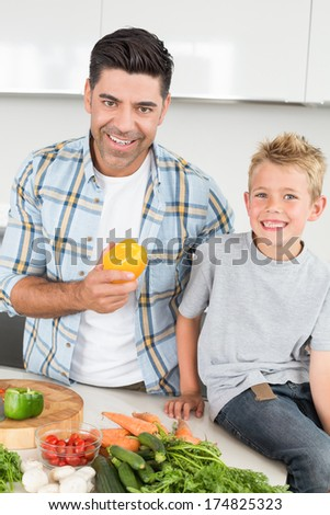Smiling father holding a yellow pepper with his son at home in kitchen - stock photo