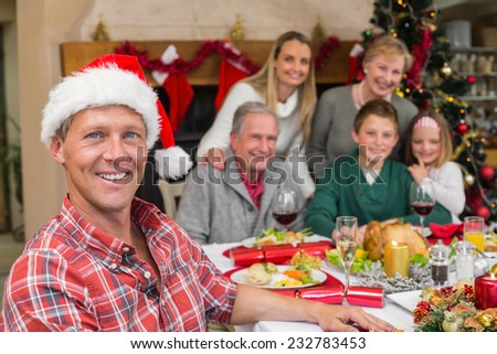 Smiling father in santa hat posing in front of his family at home in the living room - stock photo