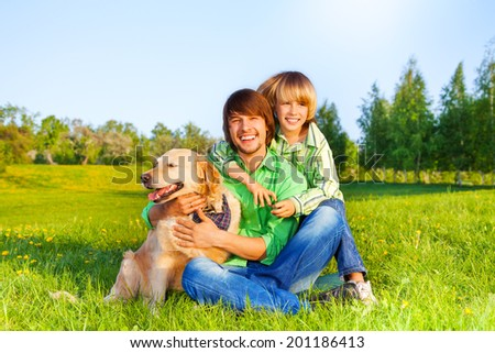 Smiling father, kid  and dog sit in park on grass - stock photo
