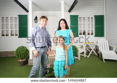 Smiling father, mother and daughter stand near porch of their new home. - stock photo