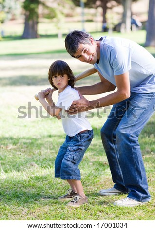 Smiling father playing baseball with his son in the park - stock photo