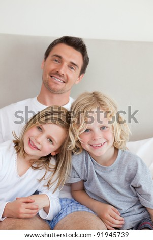 Smiling father sitting the bed together with his children - stock photo