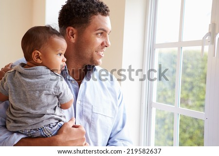 Smiling Father Standing By Window With Baby Son At Home - stock photo