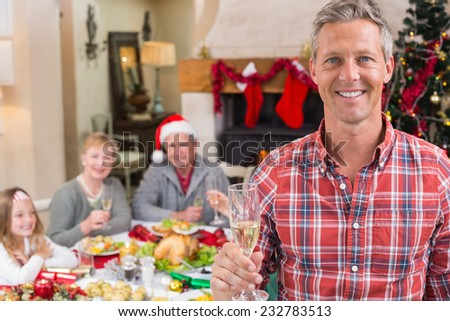 Smiling father toasting at camera in front of his family at home in the living room - stock photo