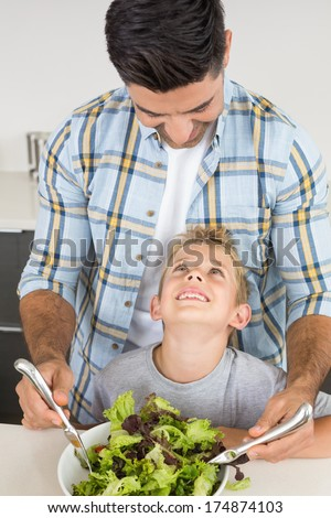 Smiling father tossing salad with his little son at home in kitchen - stock photo