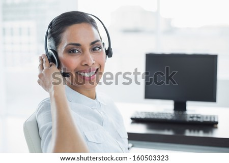Smiling female agent wearing a headset sitting in bright office looking at camera - stock photo