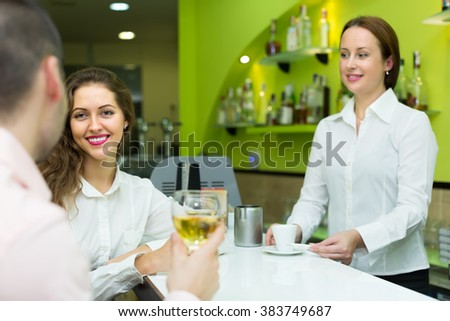Smiling female barista and two clients at counter in small bar. Focus on girl - stock photo