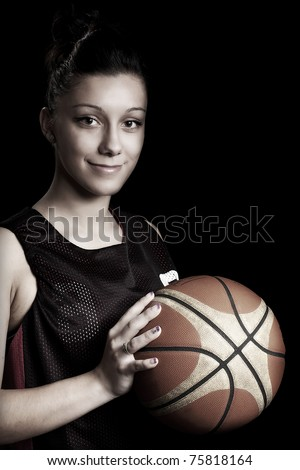 Smiling female basketball player holding ball, in black background - stock photo
