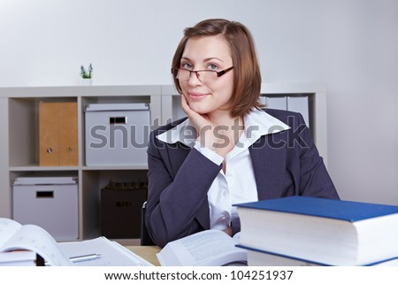 Smiling female business consultant with many books in the office - stock photo