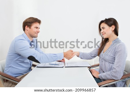Smiling female candidate shaking hands with businessman in office - stock photo