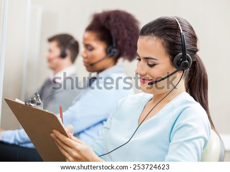 Smiling female customer service representative writing on clipboard with colleagues in background at office - stock photo