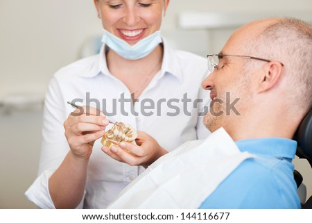 Smiling female dentist explaining artificial teeth to patient in clinic - stock photo