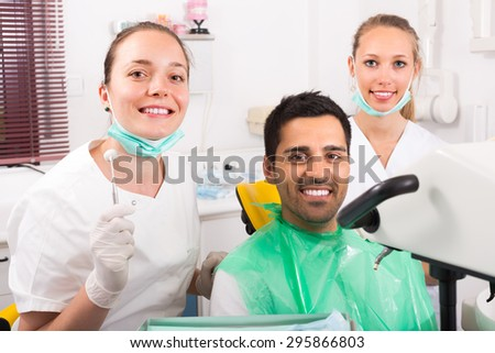 Smiling female dentist with assistant and contented patient at dental clinic
