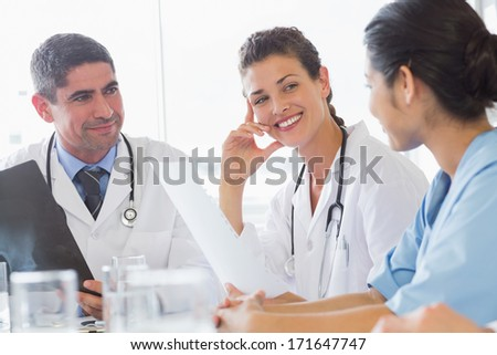 Smiling female doctor discussing with nurse and colleague in hospital - stock photo