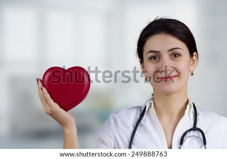 Smiling Female doctor holding red heart and a stethoscope.Medicine,Health care,Hospital. - stock photo