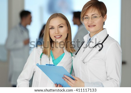 Smiling female doctors standing in the hospital, close-up - stock photo