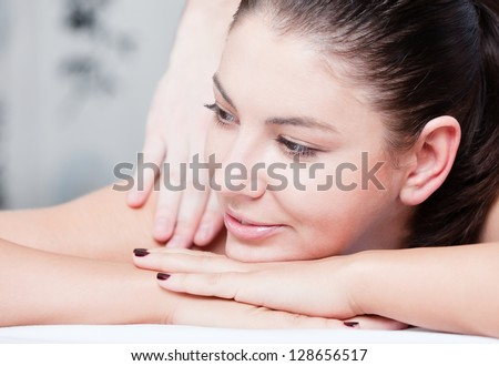 Smiling female during luxurious procedure of massage at spa salon - stock photo