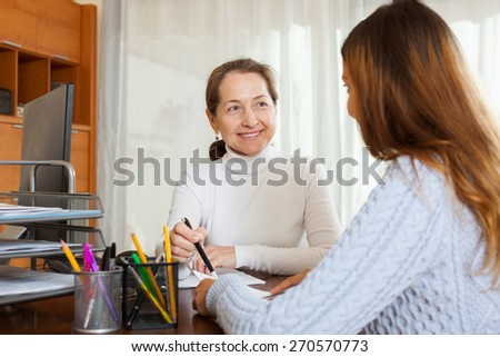 Smiling female employee talking in office with young woman  - stock photo