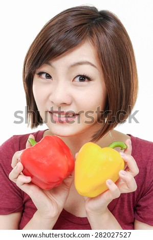 smiling female face with holding red and yellow paprika - stock photo