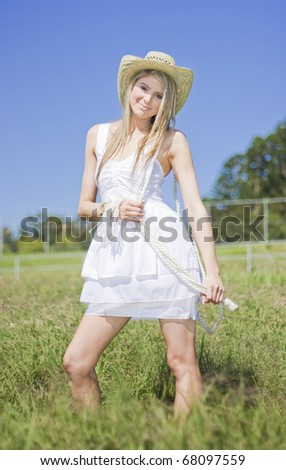 Smiling Female Farmer When Standing In The Long Grassland On A Green Farmyard Field - stock photo