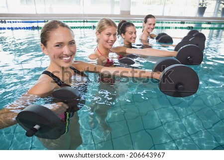 Smiling female fitness class doing aqua aerobics with foam dumbbells in swimming pool at the leisure centre - stock photo